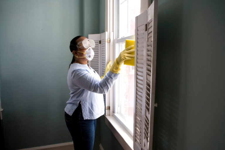 woman cleaning with mask and gloves COVID